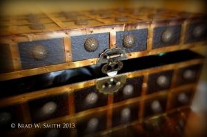 small black chest with decorative brass straps and buttons