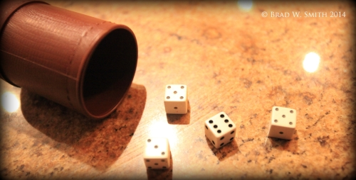 4 dice, 6, 3, 5, 5, brown cup on side, brown and black granite countertop