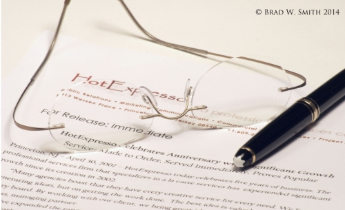wire frame glasses, high quality pen, resting on typewritten paper, copy illegible