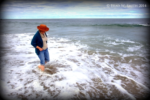 White woman, straw hat, rolled up jeans, wading at the edge of the ocean, sunny day, blue sky