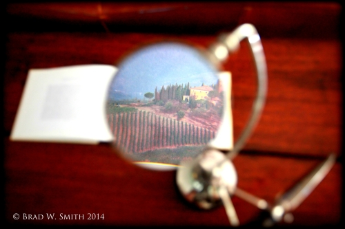 magnifying glass on stand over photo in book of a Tuscan hillside vineyard with home.