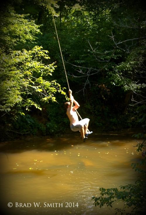 muddy creek, tree-lined, white man in shorts, shirtless