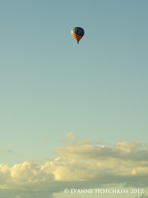 hot air balloon, American Flag motif, far away in a pale blue sky