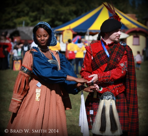 young black woman and young white man dancing outside in renaissance-period clothing.