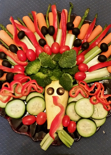 Raw carrots, cucumber, broccoli, asparagus, celery, tomatoes, summer squash, red pepper, plus black olives, arranged to look like a live turkey on platter.