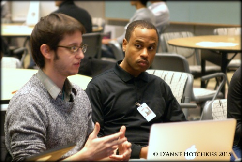 two young men, one white, one black, in discussion